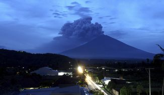 A view of Mount Agung volcano erupting in Karangasem, Bali, Indonesia, Tuesday, Nov. 28, 2017. Indonesia authorities raised the alert for the rumbling volcano to highest level on Monday and closed the international airport on tourist island of Bali stranding thousands of travelers. (AP Photo/Firdia Lisnawati)