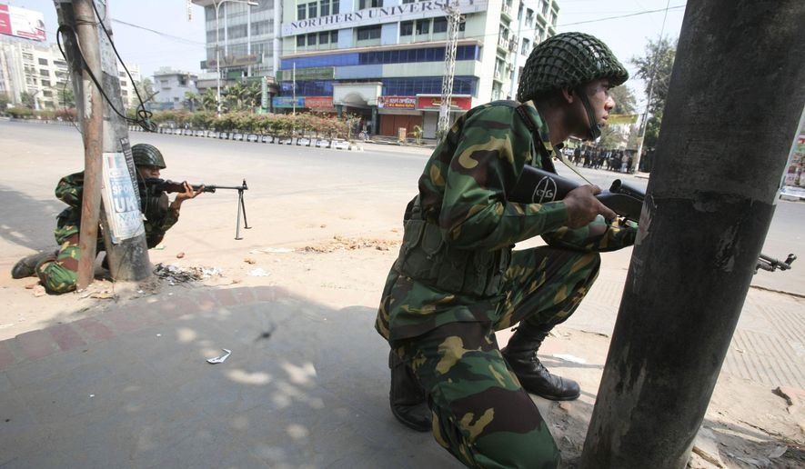 In this Feb. 25, 2009 file photo, Bangladesh army soldiers take positions near the headquarters of Bangladesh Rifles in Dhaka. In 2013, a trial court sentenced 152 people to death, but in response to an appeal, the High Court commuted the sentences for eight of them to life in prison and acquitted four others. Another man died during the 370 days of proceedings before Monday's verdict. A total of 846 people, mostly border guards, are facing trial. (AP Photo/Pavel Rahman, File)