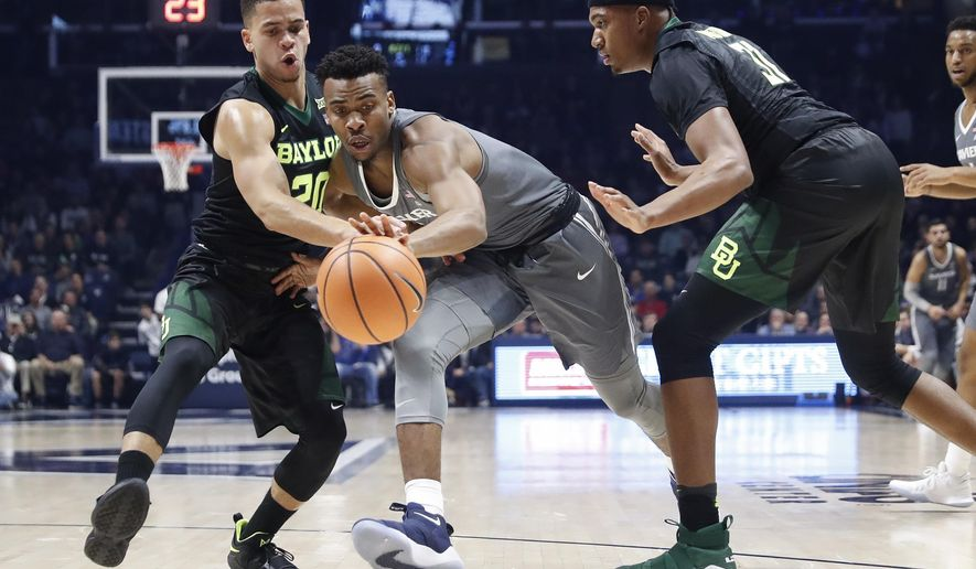 Xavier's Paul Scruggs, center, drives against Baylor's Manu Lecomte (20) in the first half of an NCAA college basketball game, Tuesday, Nov. 28, 2017, in Cincinnati. (AP Photo/John Minchillo)
