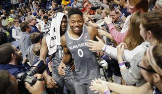 Xavier's Tyrique Jones (0) celebrates with fans after an NCAA college basketball game against Baylor, Tuesday, Nov. 28, 2017, in Cincinnati. Xavier won 76-63. (AP Photo/John Minchillo)
