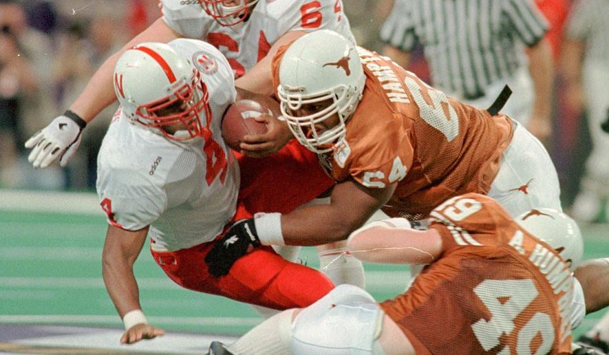 In this Dec. 7, 1996, photo, Texas' Casey Hampton, top right, and Aaron Humphrey, bottom right, combine to stop Nebraska's DeAngelo Evans at the line of scrimmage in the Big 12 Championship NCAA college football game in St. Louis. (Ralph Barrera/Austin American-Statesman via AP)