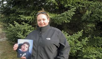 Marie Eugair poses with a photograph of her late adopted brother John Paul Greene-Eugair in Pittsford, Vt., on Tuesday, Nov. 28, 2017, in front a tree he helped plant 26 years ago. The tree was cut down on Tuesday to become Vermont's state Christmas tree. The Eugairs donated the tree in a tribute to the boy who died of complications from cerebral palsy in 1995 at age 16. (AP Photo/Lisa Rathke)