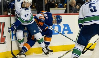 The Vancouver Canucks' Alexander Burmistrov, left, battles the New York Islanders' Anders Lee during the second period of an NHL hockey game Tuesday, Nov. 28, 2017, in New York. Right is Vancouver Canucks' Derrick Pouliot. (AP Photo/Craig Ruttle)
