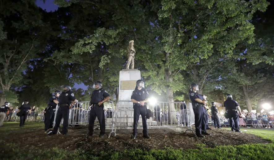 FILE - In a Tuesday, Aug. 22, 2017 file photo, police surround a Confederate monument during a protest to remove the statue at the University of North Carolina in Chapel Hill, N.C. Fearing violence or vandalism at a campus rally against a Confederate statue, two top University of North Carolina leaders, Margaret Spellings, the president of the UNC system and Carol Folt, chancellor of UNC-Chapel Hill, privately lamented their dilemma and appeared envious of another university that abruptly took down similar monuments, newly released emails show. (AP Photo/Gerry Broome, File)