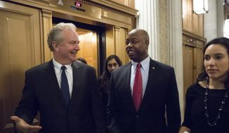 Sen. Tim Kaine, D-Va., left, and Sen. Tim Scott, R-S.C., center, head to the Senate floor for votes on Capitol Hill in Washington, Monday evening, Nov. 27, 2017. (AP Photo/J. Scott Applewhite) ** FILE **