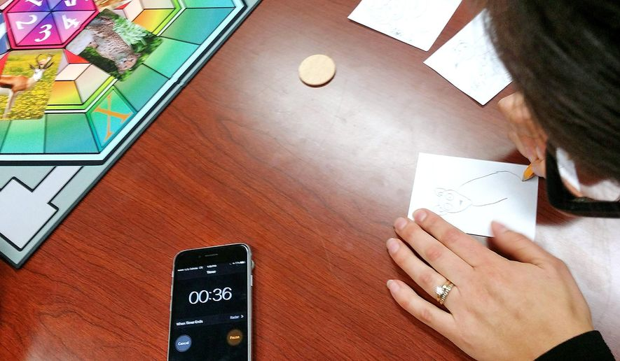 In this Nov. 22, 2017 photo, Lindsey Bussie, of Janesville, demonstrates how to play Doodle Mash, a new board game she and her husband, Jake Bussie, have invented, at the Janesville Gazette newsroom in Janesville, Wis. Bussie, a local tattoo artist, came up with the idea for Doodle Mash from a speed-sketching exercise he has used for years. (Neil Johnson/The Janesville Gazette via AP)