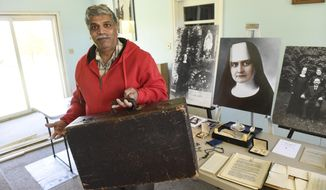 ADVANCE FOR WEEKEND EDITIONS, DEC. 2-3 - In this Oct. 24, 2017 photo, Patrick Norton holds a suitcase owned by Sister M. Annella Zervas at his home in St. Joseph, Minn. Norton says Zervas appeared to him seven years ago while he was working on campus at the College of St. Benedict. He is working to have her recognized as a saint. (Dave Schwarz/St. Cloud Times via AP)