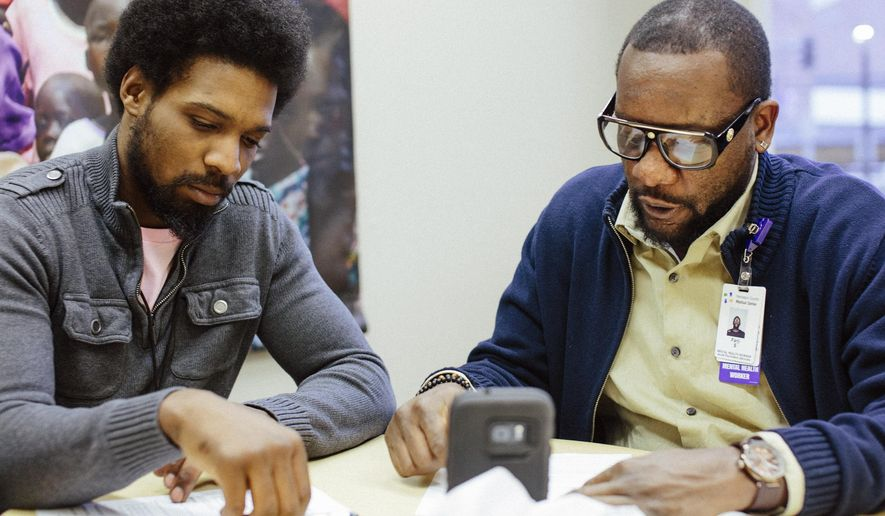 In a Friday, Nov. 17, 2017 photo, D'Andre Alexander, left, and Hennepin County Medical Center mental health worker Farji Shaheer watch a video of Farji speaking about gun violence on KMOJ inside of his office in Minneapolis. Alexander, 22, was shot in June and became paralyzed from the waist down. Shaheer is one of two counselors who staff the hospital's Next Step program, designed to support victims of gun violence. (Evan Frost/Minnesota Public Radio via AP)