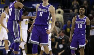 Sacramento Kings' Bogdan Bogdanovic (8) celebrates a score in the final seconds of an NBA basketball against the Golden State Warriors with Garrett Temple, left, and Frank Mason III (10) on Monday, Nov. 27, 2017, in Oakland, Calif. Sacramento won 110-106. (AP Photo/Ben Margot)