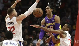 Los Angeles Lakers' Jordan Clarkson, center, passes the ball under pressure by Los Angeles Clippers' Blake Griffin, left, and Wesley Johnson during the first half of an NBA basketball game Monday, Nov. 27, 2017, in Los Angeles. (AP Photo/Jae C. Hong)