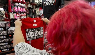 "Husker fan Brenda Saavedra holds up a shirt with the writing ""Nebraska Frost Advisory Restore Glory"" as she shops for Christmas gifts in Omaha, Neb., Tuesday, Nov. 28, 2017. Nebraska fans are gearing up for what they hope is the imminent arrival of Scott Frost as the Cornhuskers' new football coach. T-shirts imploring Frost to ""Make Nebraska Great Again"" are popular, and bars around town are setting drinks on ""Hire Scott Frost Now!"" coasters. (AP Photo/Nati Harnik)"