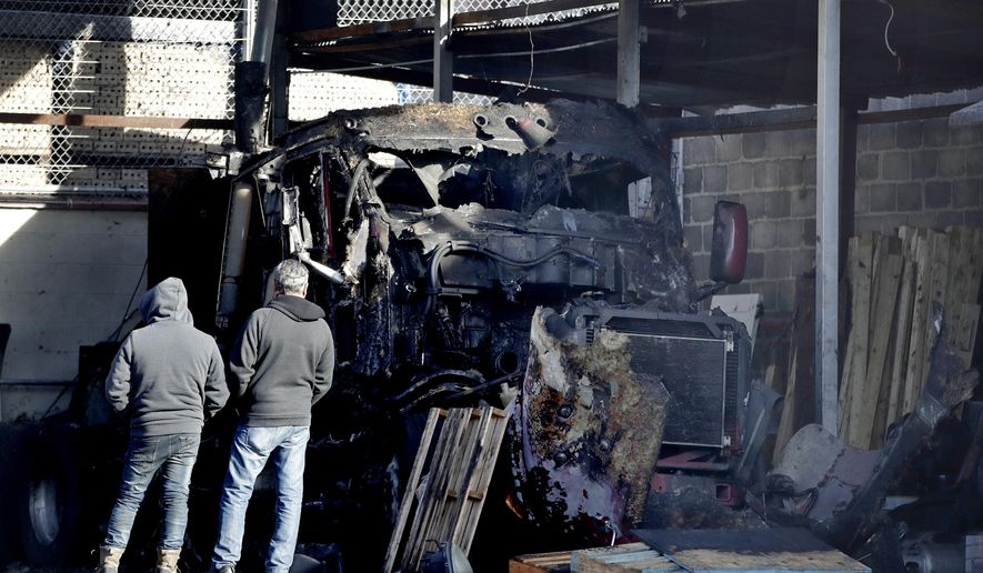 Two men look at a charred semi-tractor trailer following an early morning fire at a business, Tuesday, Nov. 28, 2017, in Newark, N.J. A vehicle and part of the commercial building also caught on fire. No injuries were reported. (AP Photo/Julio Cortez)