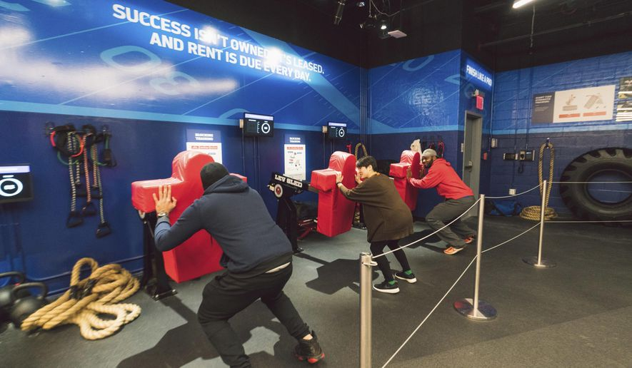 In this undated photo provided by NFL Experience Times Square, participants use football practice equipment installed at NFL Experience Times Square in New York. The $30 million project has taken 2 1/2 years to develop and has something for kids, teens and adults, mixing high tech and traditional displays into an immersive attraction. (NFL Experience Times Square via AP)