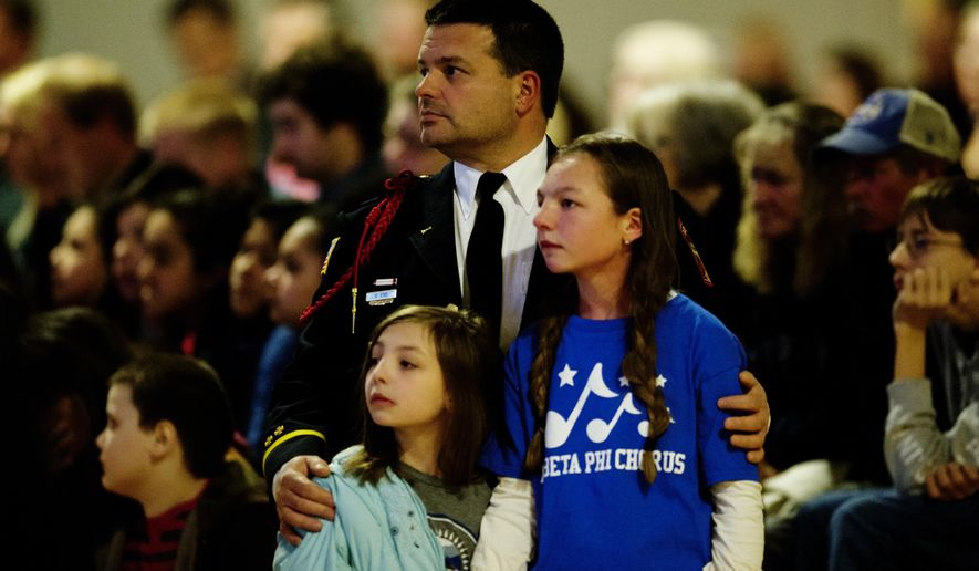 Gatlinburg firefighter Steve Ebb holds his daughters Breanna, 8, left, and Alyssa, 12, during a memorial service held at at Rocky Top Sports World marking the first anniversary of the Gatlinburg wildfire in Gatlinburg, Tenn., Tuesday, Nov. 28, 2017. The wildfires roared through Gatlinburg last November, killing 14 people in the area and damaging or destroying over 2,000 buildings. (Calvin Mattheis/Knoxville News Sentinel via AP)