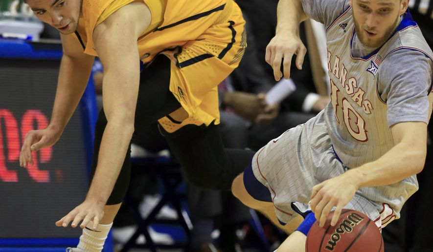Kansas guard Sviatoslav Mykhailiuk (10) steals the ball from Toledo forward Nate Navigato (35) during the first half of an NCAA college basketball game in Lawrence, Kan., Tuesday, Nov. 28, 2017. (AP Photo/Orlin Wagner)