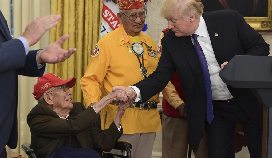 President Donald Trump meets with Navajo Code Talkers, Fleming Begaye Sr., seated and Thomas Begay, center, in the Oval Office of the White House in Washington, Monday, Nov. 27, 2017. (AP Photo/Susan Walsh)