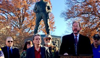 United Mine Workers of America environmental attorney Eugene Trisko speaks to a gathering of of miners in front of a statue of a coal miner, Tuesday, Nov. 28, 2017, at the state Capitol in Charleston, West Virginia. The union members held a news conference during a break in a public hearing on the Trump administration's planned repeal of an Obama-era plan to limit planet-warming carbon emissions. (AP Photo/John Raby)