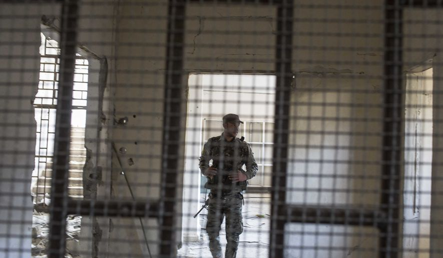 "A member of the U.S.-backed Syrian Democratic Forces (SDF) walk inside a prison built by Islamic State fighters at the stadium that was the site of IS fighters' last stand in the city of Raqqa, Syria, on Oct. 20, 2017. The SDF on Friday declared from the stadium during a ceremony the ""total liberation"" of Raqqa, the capital of the Islamic State for more than three years. (Associated Press) **FILE**"