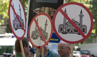 In this Aug. 18, 2012, file photo demonstrators display signs with crossed mosques during a protest in front of a mosque in Berlin, Germany. (AP Photo/Gero Breloer, file)