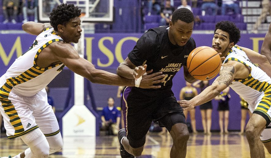 George Mason guards Otis Livingston II, left, and Jaire Grayer try to block James Madison guard Joey McLean (4) as he goes to the basket during the first half of an NCAA college basketball game Wednesday, Nov. 29, 2017, in Harrisonburg, Va. )Stephen Swofford/Daily News-Record via AP)/Daily News-Record via AP)