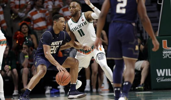 Navy's Shawn Anderson (20) drives as Miami's Bruce Brown Jr. (11) defends during the first half of an NCAA college basketball game, Sunday, Nov. 12, 2017 photo, in Coral Gables, Fla. (AP Photo/Lynne Sladky)