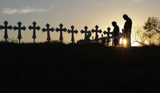 Kenneth and Irene Hernandez pay their respects as they visit a makeshift memorial with crosses placed near the scene of a shooting at the First Baptist Church on Nov. 6, 2017, in Sutherland Springs, Texas. A man opened fire inside the church in the small South Texas community killing more than two dozen and injuring others. (AP Photo/Eric Gay) ** FILE **