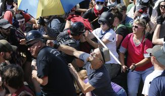 White nationalist protesters clash with counterprotesters at the entrance to Lee Park in Charlottesville, Va., on Aug. 12, 2017. Gov. Terry McAuliffe declared a state of emergency and police in riot gear ordered people to disperse after the chaotic violent clashes. (AP Photo/Steve Helber)