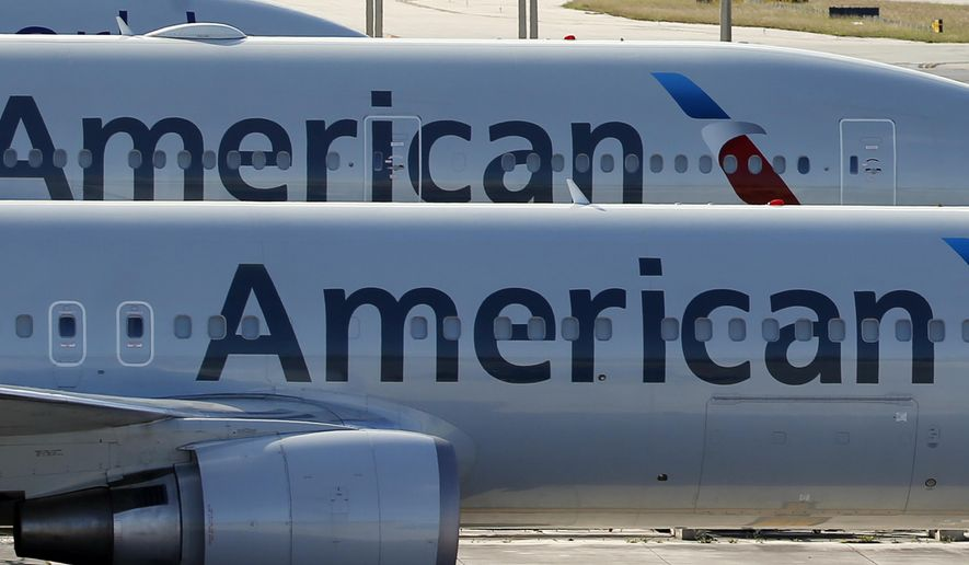 FILE - In this Monday, Nov. 6, 2017, file photo, a pair of American Airlines jets are parked on the airport apron at Miami International Airport in Miami. A scheduling glitch has left American scrambling to find pilots to operate thousands of flights over the busy Christmas holiday period. American said Wednesday, Nov. 29, 2017, it expects to avoid canceling flights by paying overtime and using reserve pilots. (AP Photo/Wilfredo Lee, File)