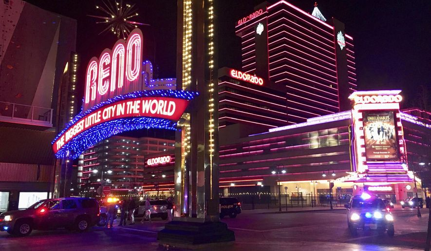 Law enforcement block downtown Reno, Nev., streets during an active shooter response at the Montage apartment building, Tuesday, Nov. 28, 2017. A suspect is in custody after opening fire for at least 20 minutes Tuesday night, but there are no reports of any injuries, authorities said. The shots were fired at the Montage, a building in downtown Reno where SWAT teams and news vans have gathered. (Andy Barron/The Reno Gazette-Journal via AP)