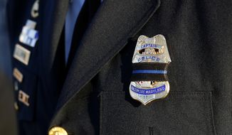 Baltimore Police Capt. Jarron Jackson wears a black mourning band across his badge before Baltimore Police Detective Sean Suiter's funeral at Mount Pleasant Church in Baltimore, Wednesday, Nov. 29, 2017. Suiter died a day after being shot while investigating a homicide case in a particularly troubled area of west Baltimore. (AP Photo/Patrick Semansky) ** FILE **