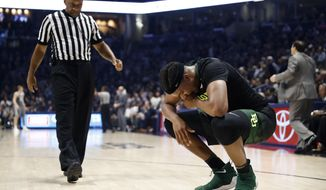 Baylor's Terry Maston, right, winces in pain in the second half of an NCAA college basketball game against Xavier, Tuesday, Nov. 28, 2017, in Cincinnati. Xavier won 76-63. (AP Photo/John Minchillo)