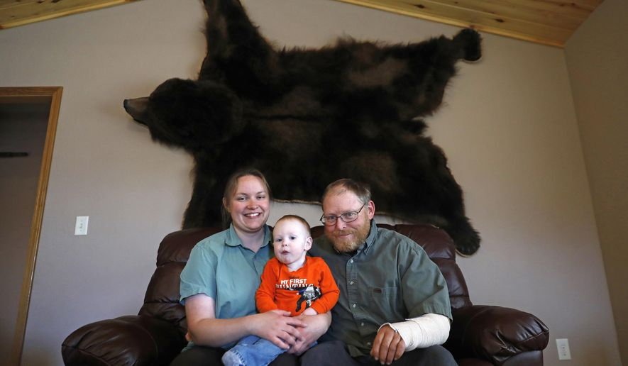 In this photo taken Nov. 16, 2017, Genevieve, left, Asher, 1, center, and Jonathan Sheets, right, sit for a portrait beneath an Alaskan brown bear pelt Genevieve bagged in 2011 in their home in Powell, Wyo. (Rebecca Noble/The Cody Enterprise via AP)