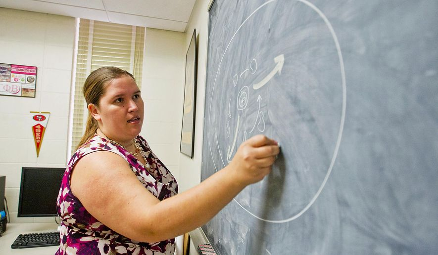 In this Nov. 16, 2017 photo, Ph.D. student Michelle Mason draws a diagram of a quasar on a chalkboard in her office in the University of Wyoming's Physical Science Building, in Laramie, Wyo. (Shannon Broderick/Laramie Daily Boomerang via AP)