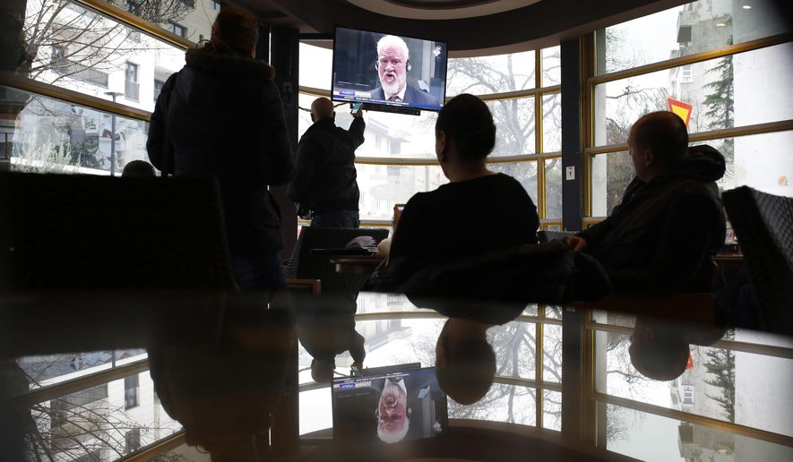 "Bosnian people from west part of Mostar watch the live TV broadcast from the International Criminal Court for the former Yugoslavia (ICTY) in The Hague as Slobodan Praljak brings a bottle to his lips, in southern Bosnian town of Mostar 140 kms south of Sarajevo, on Wednesday, Nov. 29, 2017. Praljak yelled, ""I am not a war criminal!"" and appeared to drink from a small bottle, seconds after judges reconfirmed his 20-year prison sentence for involvement in a campaign to drive Muslims out of a would-be Bosnian Croat ministate in Bosnia in the early 1990s. Croatia's state TV says Praljak who claimed to have taken poison just after his 20-year sentence was upheld by appeals judges at a U.N. war crimes tribunal, has died. (AP Photo/Amel Emric)"