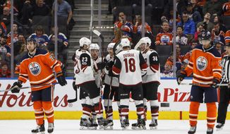 Phoenix Coyotes players celebrate a goal as Edmonton Oilers' Iiro Pakarinen (26) and Leon Draisaitl (29) skate past during the second period of an NHL hockey game in Edmonton, Alberta, Tuesday, Nov. 28, 2017. (Jason Franson/The Canadian Press via AP)