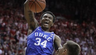 Duke's Wendell Carter Jr. dunks next to Indiana's Collin Hartman during the first half of an NCAA college basketball game, Wednesday, Nov. 29, 2017, in Bloomington, Ind. (AP Photo/Darron Cummings)
