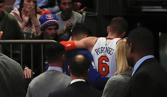 New York Knicks forward Kristaps Porzingis (6) is helped off the court after turning an ankle against the Miami Heat during the first quarter of an NBA basketball game, Wednesday, Nov. 29, 2017, in New York. (AP Photo/Julie Jacobson)
