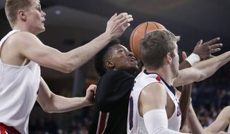 Gonzaga center Jacob Larsen, left, guard Jesse Wade, right, and Incarnate Word forward Simi Socks go after a rebound during the first half of an NCAA college basketball game in Spokane, Wash., Wednesday, Nov. 29, 2017. (AP Photo/Young Kwak)