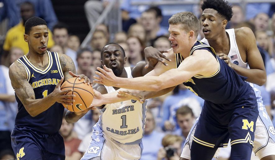 North Carolina's Theo Pinson (1) and Sterling Manley, right, reach for the ball with Michigan's Charles Matthews (1) and Moritz Wagner during the first half of an NCAA college basketball game in Chapel Hill, N.C., Wednesday, Nov. 29, 2017. (AP Photo/Gerry Broome)