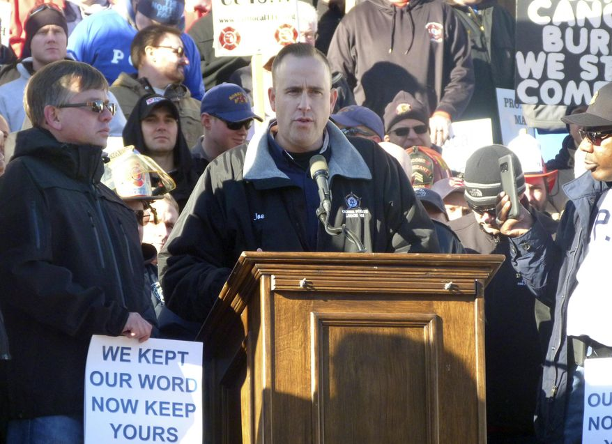 Joe Adams, a Grosse Pointe, Mich., police officer and president of the Michigan Fraternal Order of Police, speaks at a rally at the Michigan Capitol, Wednesday, Nov. 29, 2017, in Lansing, Mich. Police and firefighters are concerned that legislation, which has not been introduced but which is being drafted by Republican lawmakers, could lead to retiree health care cuts as part of efforts to address municipalities' unfunded liabilities. (AP Photo/David Eggert)