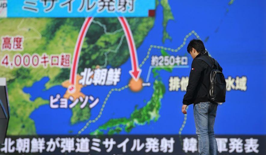 A man stands in front of a huge screen showing TV news program reporting North Korea's missile launch, in Tokyo, Wednesday, Nov. 29, 2017. (AP Photo/Shizuo Kambayashi)