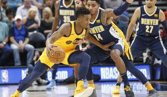 Utah Jazz guard Donovan Mitchell, left, drives around Denver Nuggets guard Gary Harris (14) in the first half during an NBA basketball game Tuesday, Nov. 28, 2017, in Salt Lake City. (AP Photo/Rick Bowmer)