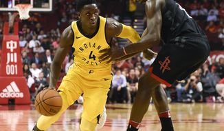 Indiana Pacers guard Victor Oladipo (4) dribbles around Houston Rockets center Clint Capela during the first half of an NBA basketball game, Wednesday, Nov. 29, 2017, in Houston. (AP Photo/Eric Christian Smith)