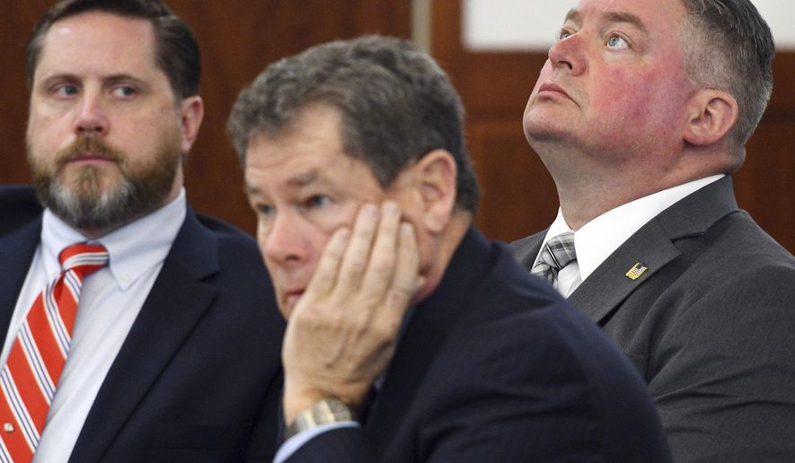 Former Worcester police officer Michael J. Motyka, right, looks skyward alongside his defense attorneys James J. Gribouski, center, and James A. Walckner, left, during his sentencing, Wednesday, Nov. 29, 2017 in Worcester, Mass. Motyka was sentenced to two years of probation for beating a shackled prisoner in his cell. (Christine Hochkeppel/Worcester Telegram & Gazette via AP)