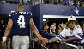 FILE - In this Nov. 23, 2017, file photo, Dallas Cowboys quarterback Dak Prescott (4) shakes hands with fans as he walks into the team's clubhouse after  28-6 loss to the Los Angeles Chargers in an NFL football game, in Arlington, Texas. Prescott and the Cowboys have already lost all realistic hope of defending their NFC East title. A loss to Washington on Thursday night, Nov. 30, would officially hand the crown to Philadelphia with a month to go. (AP Photo/Ron Jenkins, File)