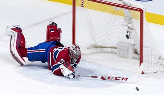 Montreal Canadiens goaltender Carey Price dives to deflect a shot as they face the Ottawa Senators during the third period of an NHL hockey game in Montreal on Wednesday, Nov. 29, 2017. (Paul Chiasson/The Canadian Press via AP)