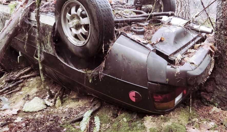 This undated photo provided by the Jackson County Sheriff's Office shows a 1979 Porsche 924 in a wooded area near Trail, Ore. The Porsche, stolen nearly 27 years ago from a movie theatre parking lot in Medford, Ore., was discovered at the bottom of a steep, forested cliff by a man walking his dog. (Jackson County Sheriff's Office via AP)