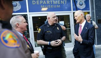 Florida Gov. Rick Scott, right, talks with Tampa Police Chief Brian Dugan, center, and Tampa Mayor Bob Buckhorn, left, outside Tampa Police Headquarters in Tampa, Fla. on Wednesday, Nov. 29, 2017. Scott's visit followed the announcement of the arrest in the Seminole Heights murders. (Will Vragovic/Tampa Bay Times via AP)