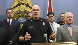 Tampa Police Chief Brian Dugan, center, along with Mayor Bob Buckhorn, right, announce that they intend to charge Howell Emanuel Donaldson, 24, with four counts of first degree murder in connection with the Seminole Heights homicides, Tuesday, Nov. 28, 2017, in Tampa, Fla. Police detained the man earlier Tuesday after a tip that he had a gun at a McDonald's. Four people have been killed in the neighborhood since Oct. 9.  (Chris Urso/Tampa Bay Times via AP)