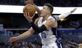 Orlando Magic's Aaron Gordon (00) goes up for a shot past Oklahoma City Thunder's Andre Roberson during the second half of an NBA basketball game, Wednesday, Nov. 29, 2017, in Orlando, Fla. Orlando won 121-108. (AP Photo/John Raoux)